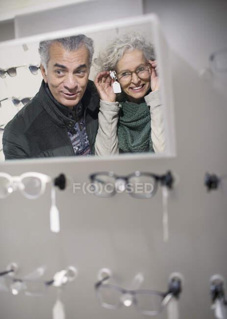 Couple sénior magasinant pour des lunettes dans un magasin d'optométrie — Photo de stock