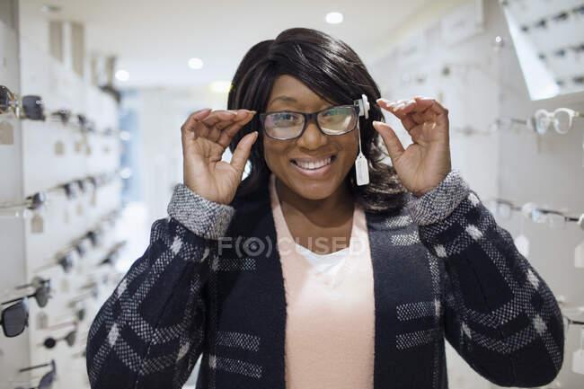 Portrait femme confiante faisant des achats de lunettes dans un magasin d'optométrie — Photo de stock
