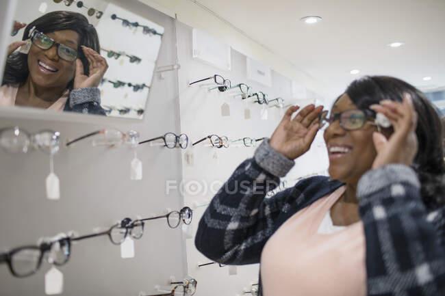 Donna sorridente che prova gli occhiali nel negozio di optometria — Foto stock