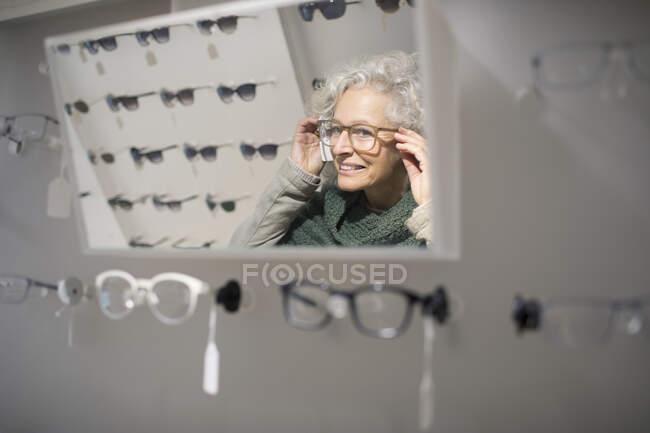 Donna anziana che prova gli occhiali nel negozio di optometria — Foto stock