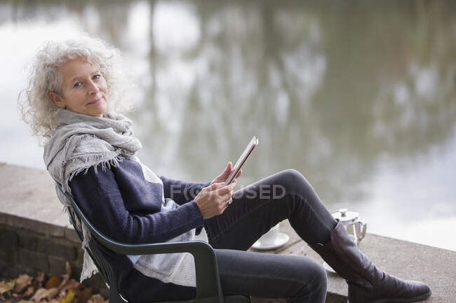 Portrait confident active senior woman using digital tablet at park pond — Stock Photo