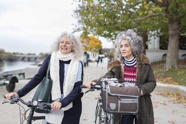 Активні старші жінки друзі на велосипедах в осінньому парку. — стокове фото