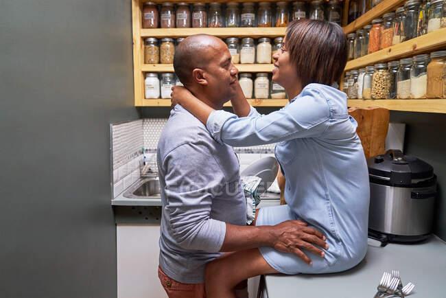 Casal afetuoso abraçando e falando na cozinha — Fotografia de Stock