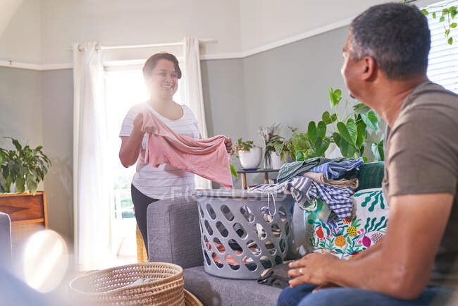 Mature couple talking and folding laundry in living room — Stock Photo