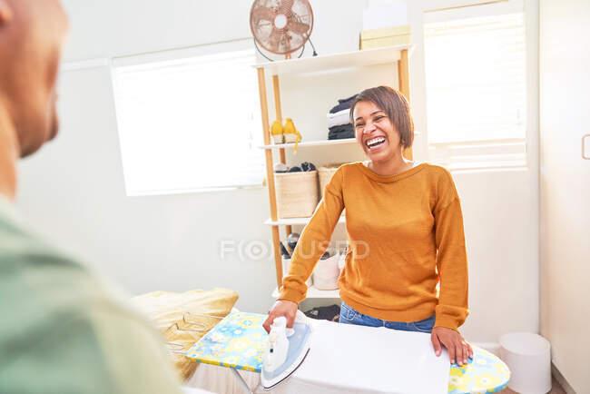 Mulher feliz passar roupas em casa — Fotografia de Stock
