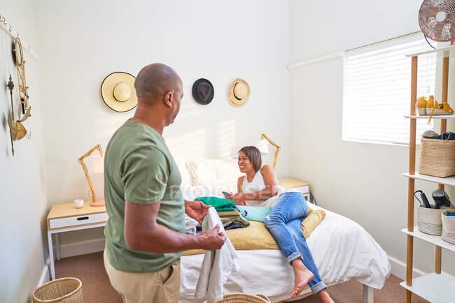 Lavanderia casal feliz dobrável e relaxante na cama — Fotografia de Stock