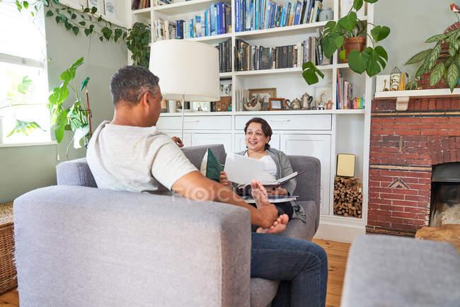 Coppia che parla e legge sul divano del salotto — Foto stock