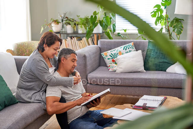 Affectionate couple reading in living room — Stock Photo