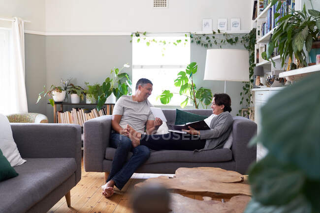 Happy mature couple using digital tablet on living room sofa — Stock Photo