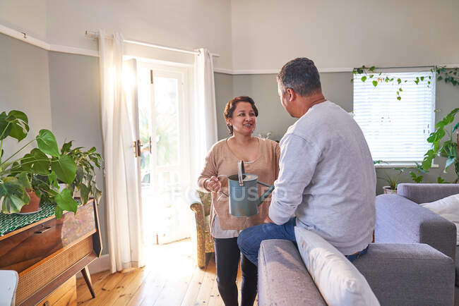 Mature couple watering plants and talking in living room — Stock Photo