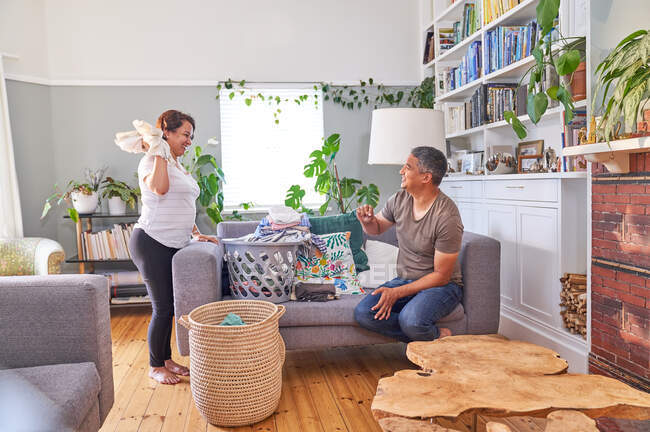 Playful mature couple folding laundry in living room — Stock Photo