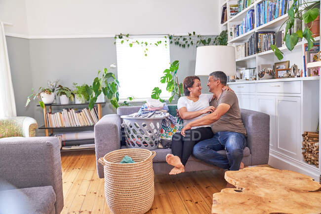 Affectionate mature couple doing laundry on living room sofa — Stock Photo