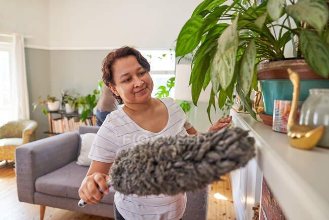Зрелая женщина с пыльной пыльной гостиной — стоковое фото