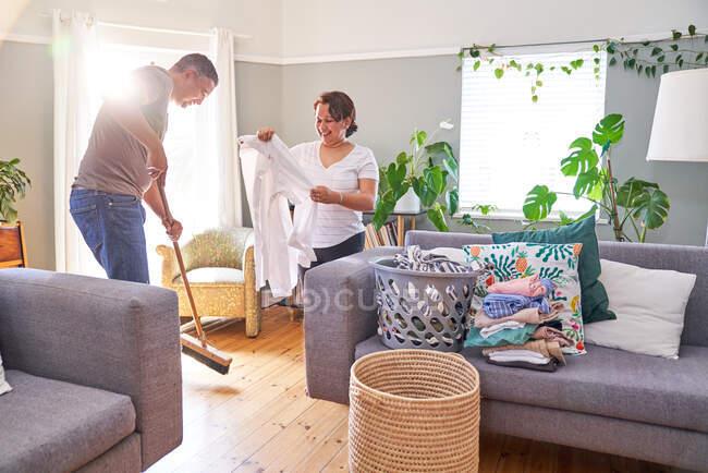 Maduro casal dobrável lavandaria e varrendo sala de estar — Fotografia de Stock