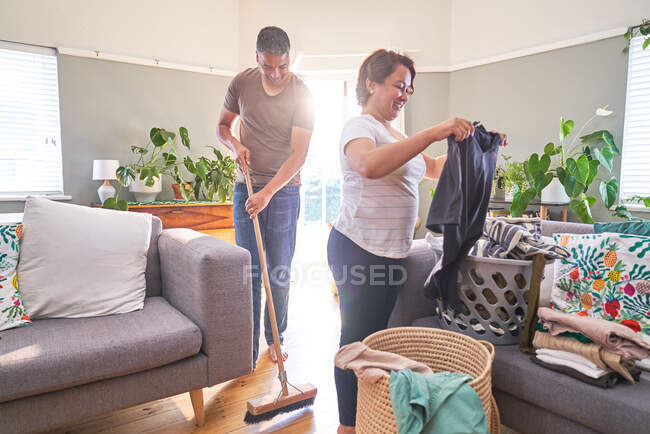 Mature couple folding laundry and sweeping living room — Stock Photo