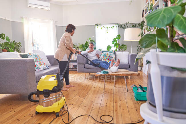Woman vacuuming and talking to husband in living room — Stock Photo