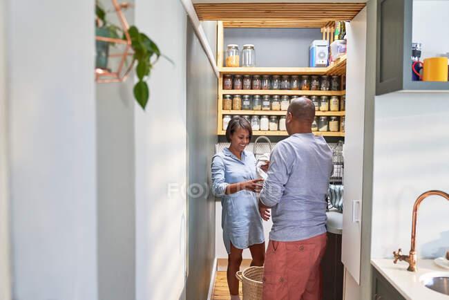 Casal fazendo pratos e lavanderia na cozinha — Fotografia de Stock