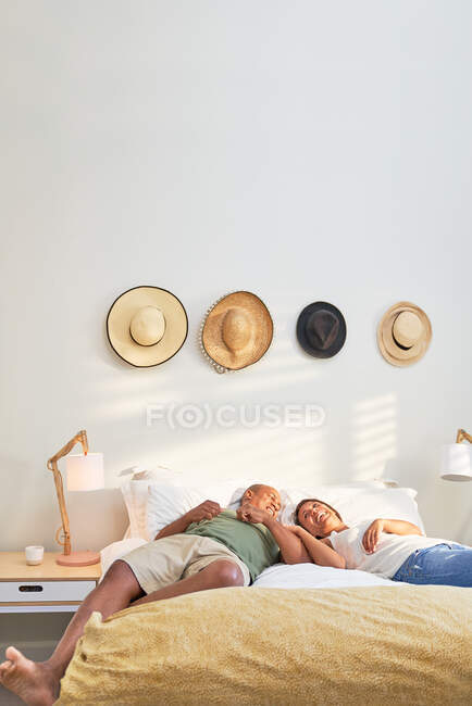 Feliz afetuoso casal relaxar e falar na cama — Fotografia de Stock