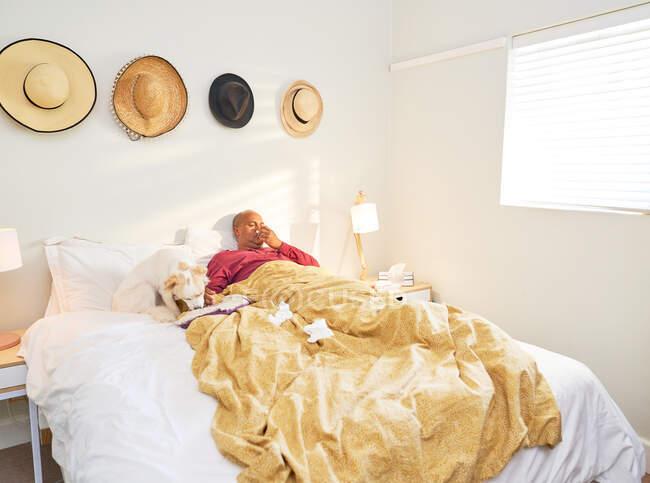 Enferma homem soprando nariz com tecidos na cama — Fotografia de Stock