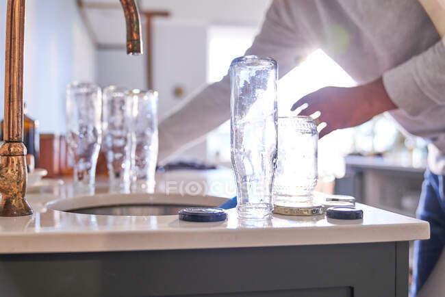 Homem lavando garrafas de vidro na pia da cozinha — Fotografia de Stock