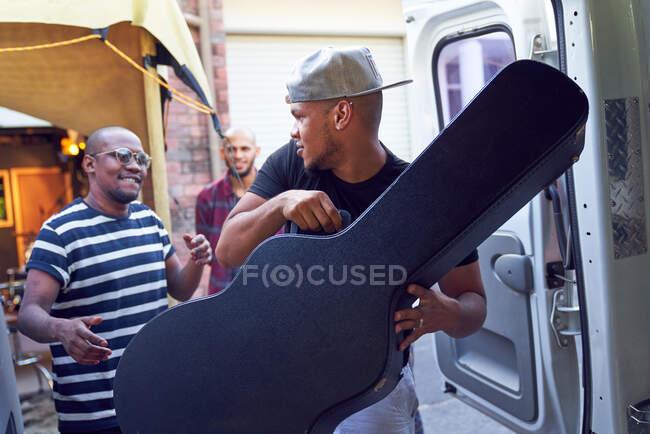 Музиканти завантажують гітарні портфелі в фургон. — стокове фото