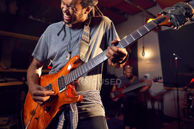 Male musician playing electric guitar in recording studio — Stock Photo