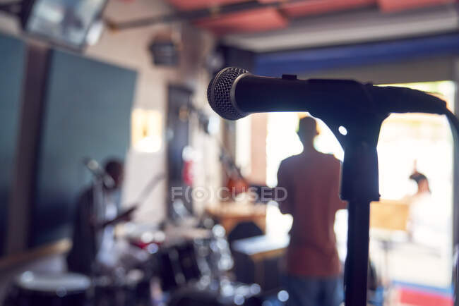 Microphone and musicians in garage recording studio — Stock Photo