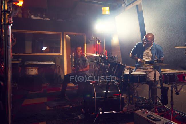 Чоловічі музиканти грають на гітарі та барабанах у студії звукозапису. — стокове фото