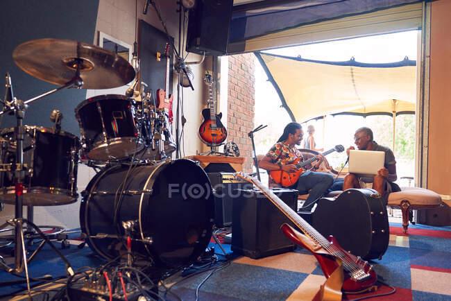 Músicos masculinos que practican en el estudio de grabación de garaje - foto de stock