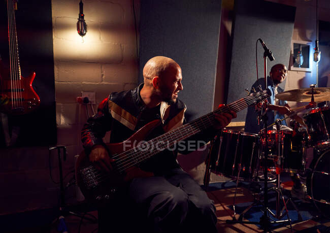 Male musician playing guitar in recording studio — Stock Photo