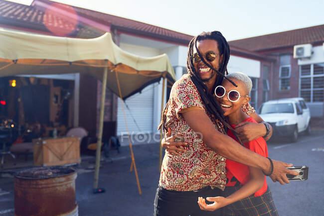 Портрет счастливых друзей, обнимающихся на солнечной парковке — стоковое фото