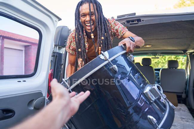 Щасливий чоловічий музикант завантажує барабани в фургон — стокове фото