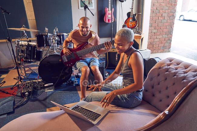 Música sonriente con ordenador portátil y guitarra en estudio de grabación. - foto de stock