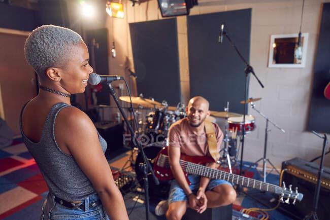 Músicos sonrientes que practican en estudios de grabación - foto de stock