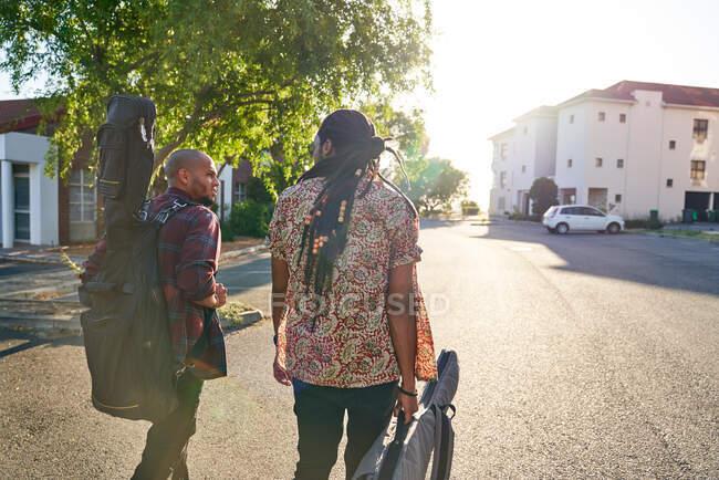 Чоловічі музиканти з гітарними скриньками ходять по сонячній вулиці. — стокове фото