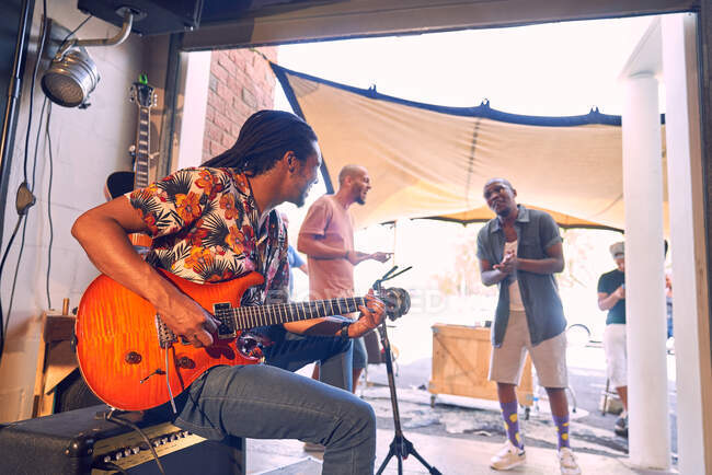 Музиканти репетирують і розмовляють в гаражній студії звукозапису. — стокове фото