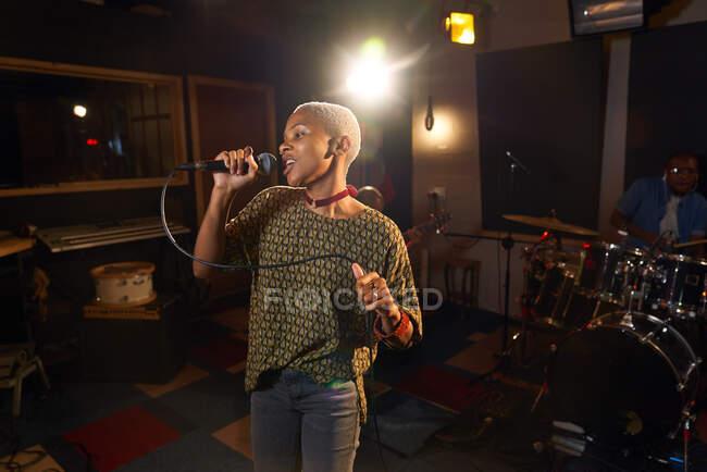Música femenina cantando al micrófono en el estudio de grabación - foto de stock