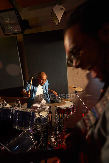 Male musician playing drums in recording studio — Stock Photo