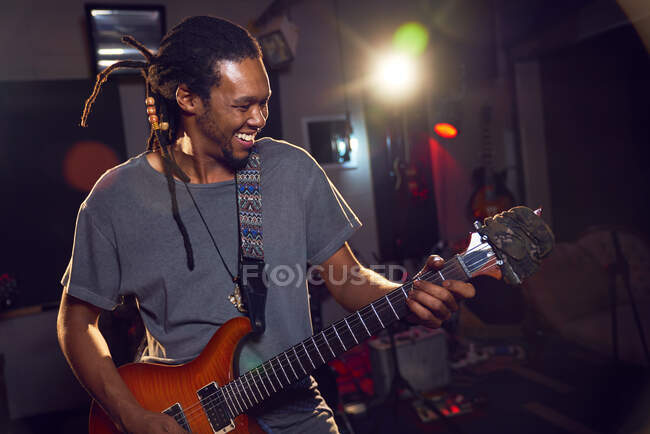 Happy male musician playing electric guitar in recording studio — Stock Photo