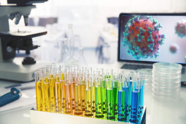 Multicolor vials on laboratory table next to coronavirus on screen — Stock Photo