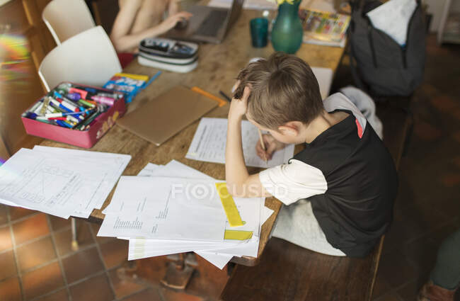 Boy homeschooling at dining table — Stock Photo