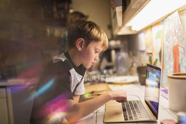 Menino focado fazendo lição de casa no laptop na cozinha — Fotografia de Stock