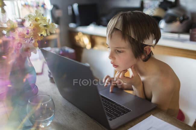 Menino curioso homeschooling no laptop na cozinha — Fotografia de Stock