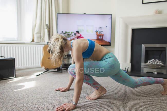Mulher praticando ioga online na sala de estar — Fotografia de Stock