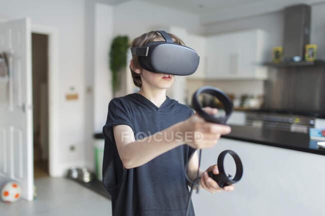 Menino com óculos VRS jogando videogame — Fotografia de Stock