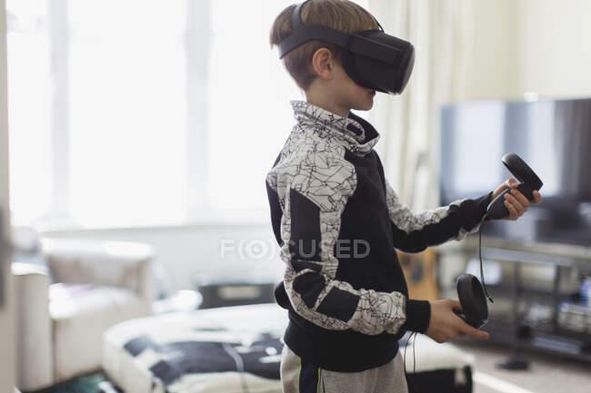 Menino jogando jogo de vídeo com óculos VRS na sala de estar — Fotografia de Stock