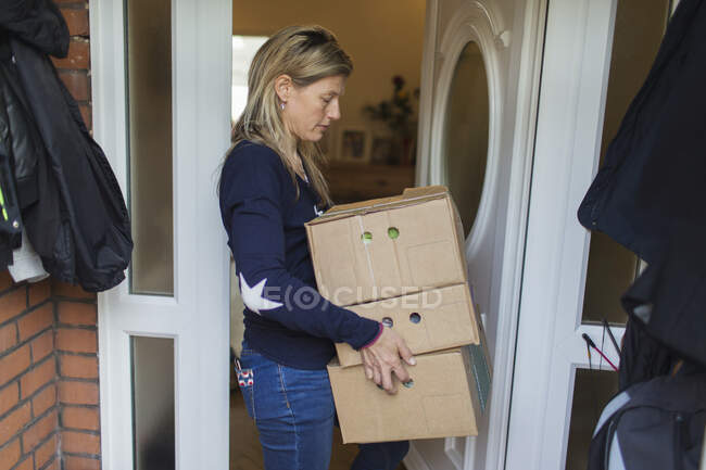 Woman retrieving produce boxes at front stoop — Stock Photo