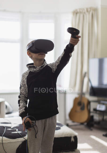 Boy playing video game with VRS goggles in living room — Stock Photo
