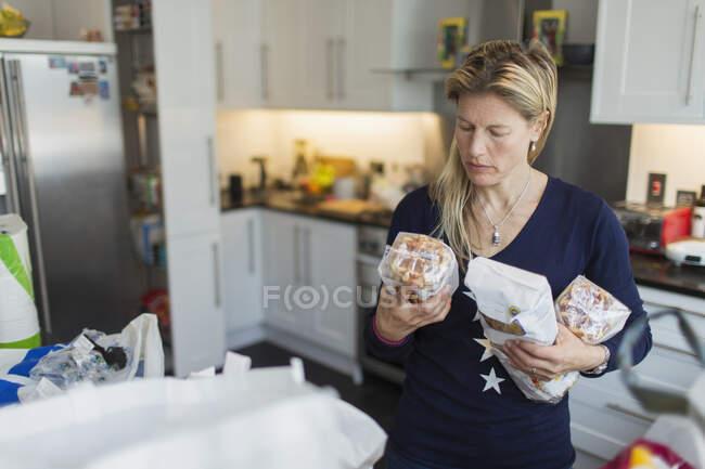 Mulher descarregar mantimentos na cozinha — Fotografia de Stock