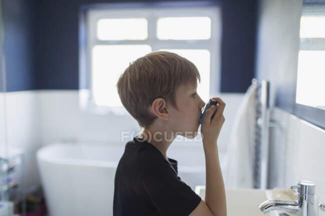 Menino com asma usando inalador no banheiro — Fotografia de Stock